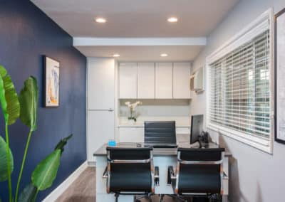 Leasing office with Navy blue wall, one desk, and two chairs
