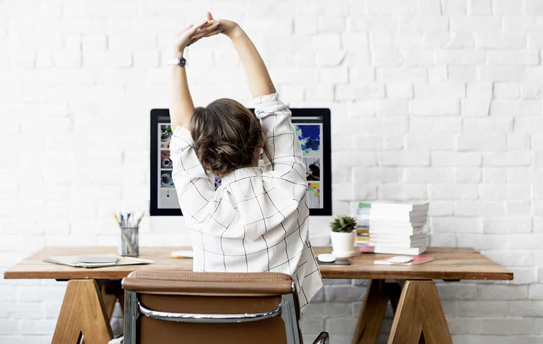 woman sitting in front of computer and stretch oneself after long working day