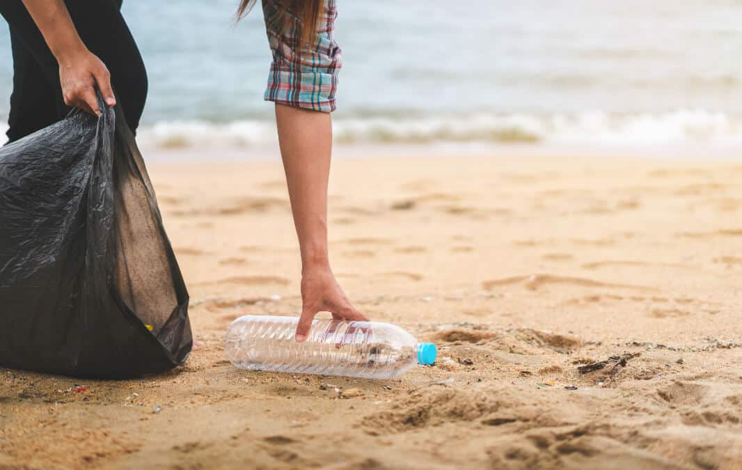 Woman picking an empty bottle at the beach